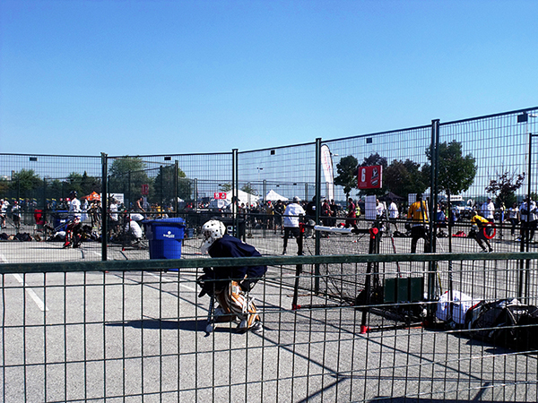 Temporary metal fence forms the perimeter of a road hockey rink, where a goalie is seen defending his net