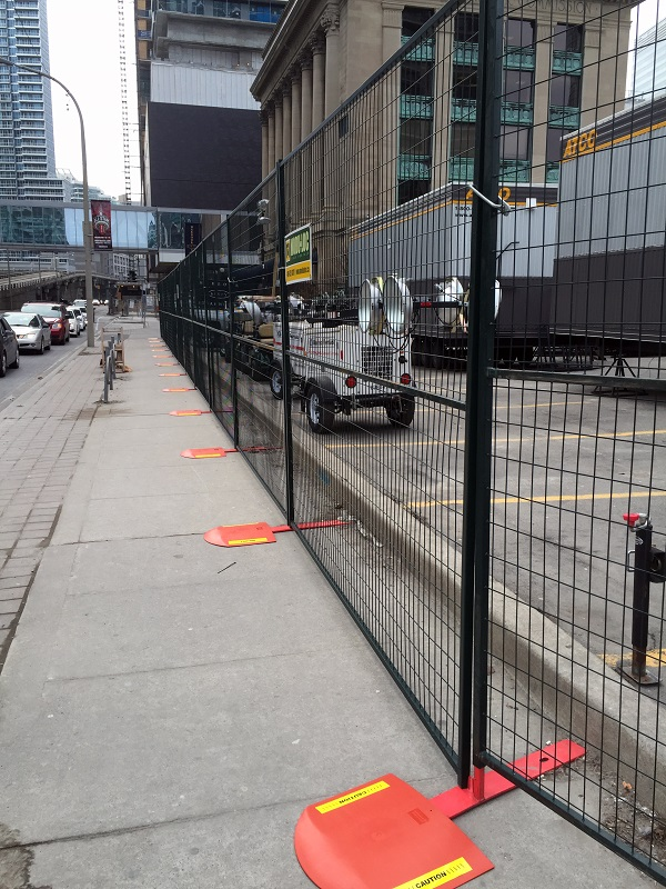 8' tall temporary metal fence surrounds a parking lot, where media trailers are parked