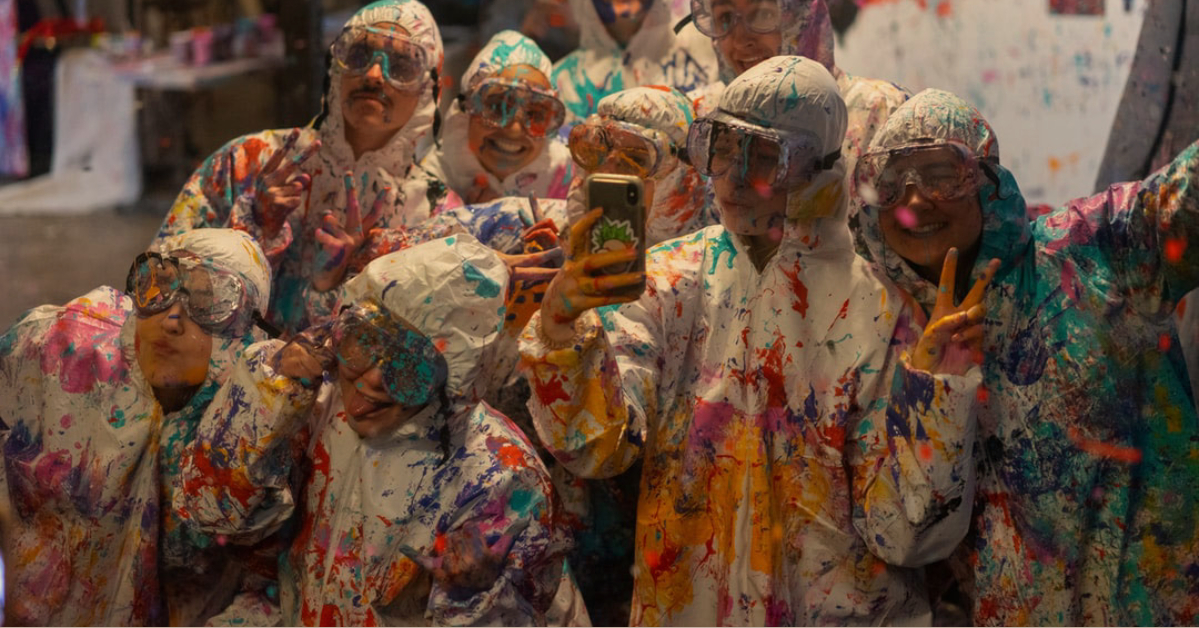 Group of people wearing safety glasses and coveralls and covered in paint splatter