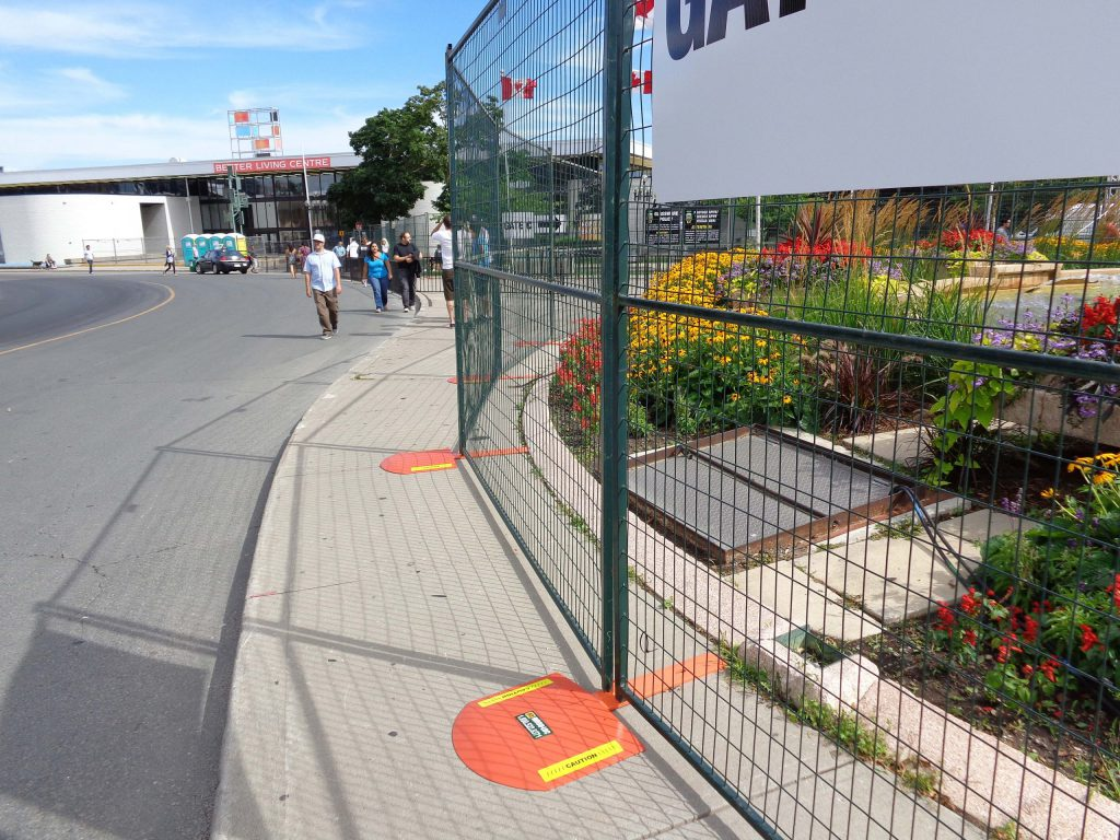 Temporary fencing surrounds a garden. Plastic orange safety ramps cover the fence bases.