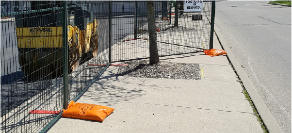 Sandbags help weigh down temporary fence bases