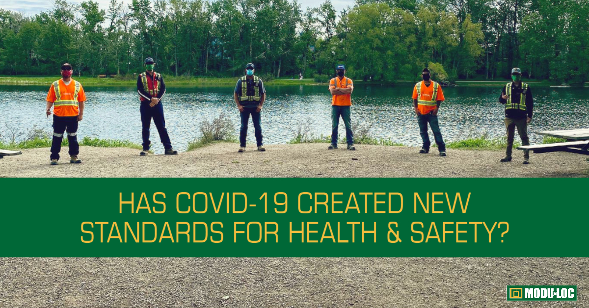 "Six Modu-Loc employees stand 2 metres apart in front of a lake, with the title ""Has COVID-19 Created New Standards for Health & Safety?"""