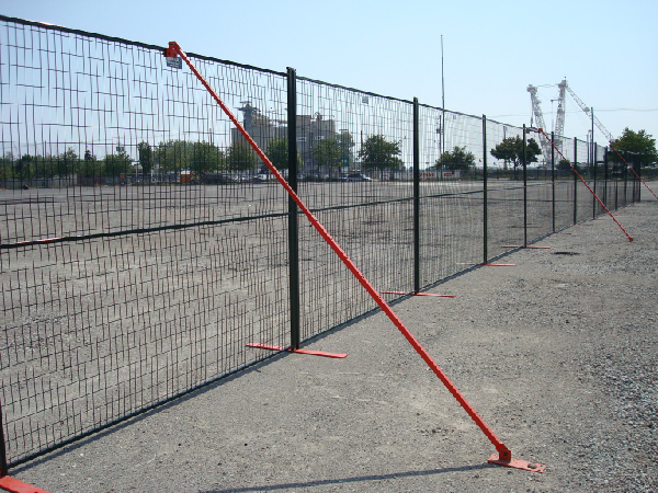 Wind braces secure temporary fence panels to the ground