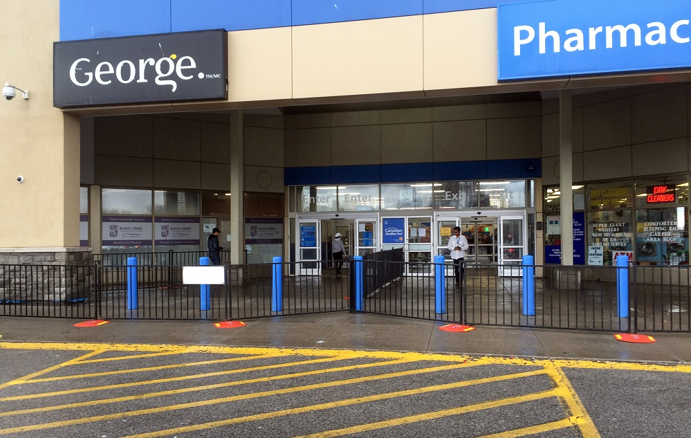 A photo of a large retail store with temporary fence being used to designate the entrance and exit