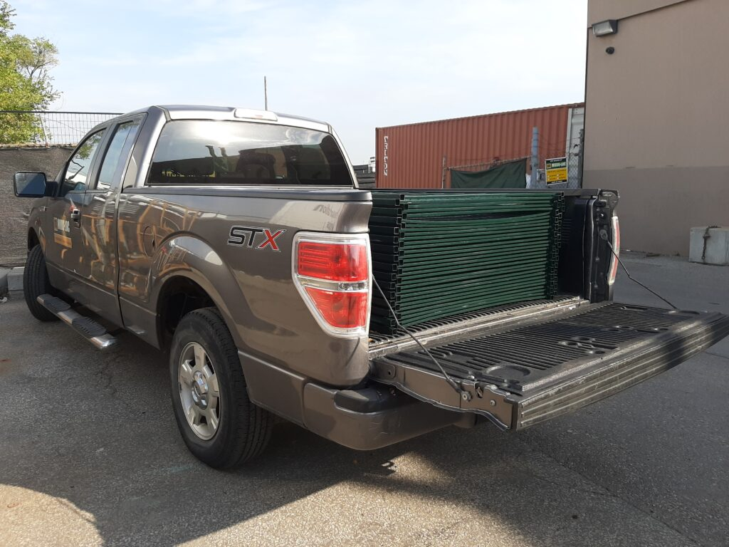 A pickup truck with a stack of metal fence panels in the truck bed