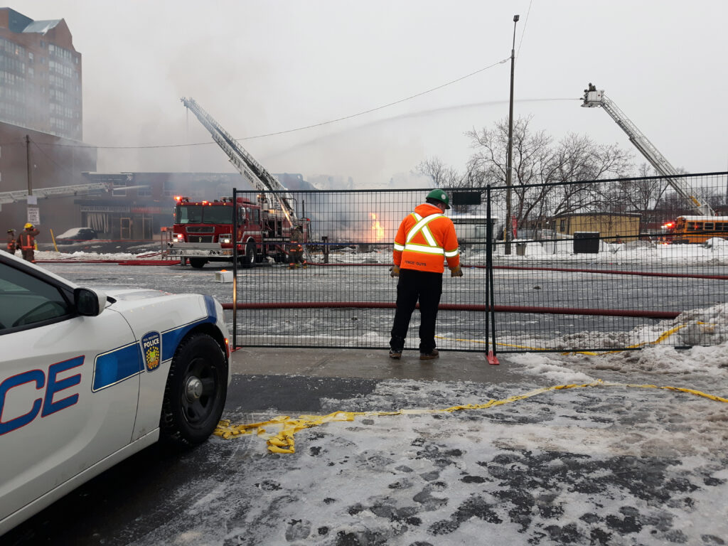 A fence installer placing a temporary fence panel on an emergency job. A fire is seen in the background and a police car is parked in front of the fence.