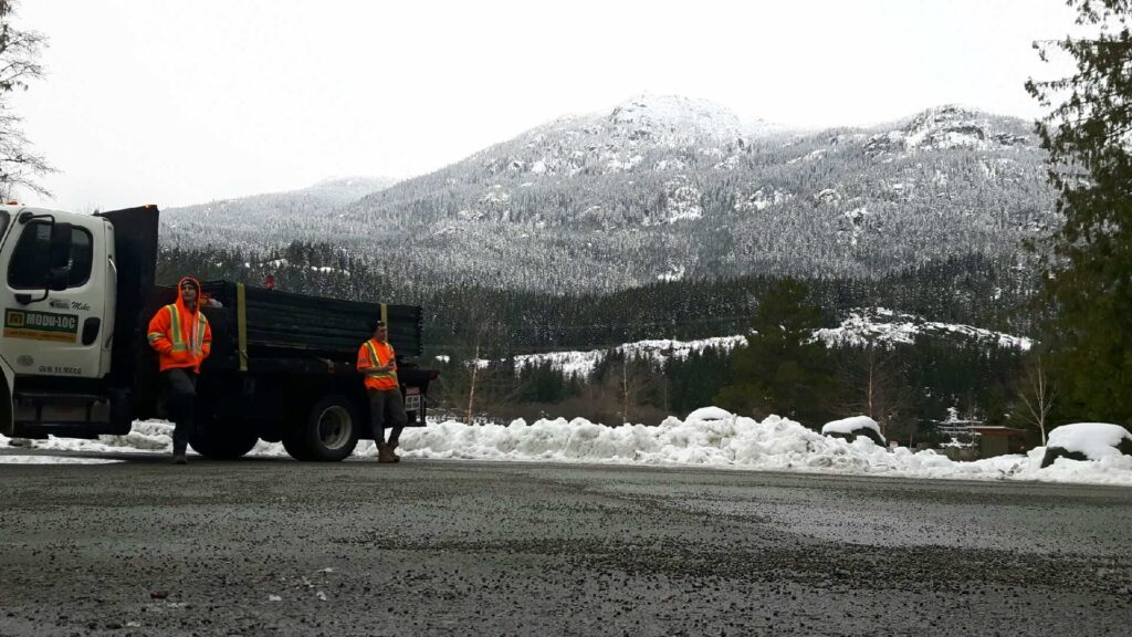 Two fence installers stand with their truck. Mountains are visible in the background.