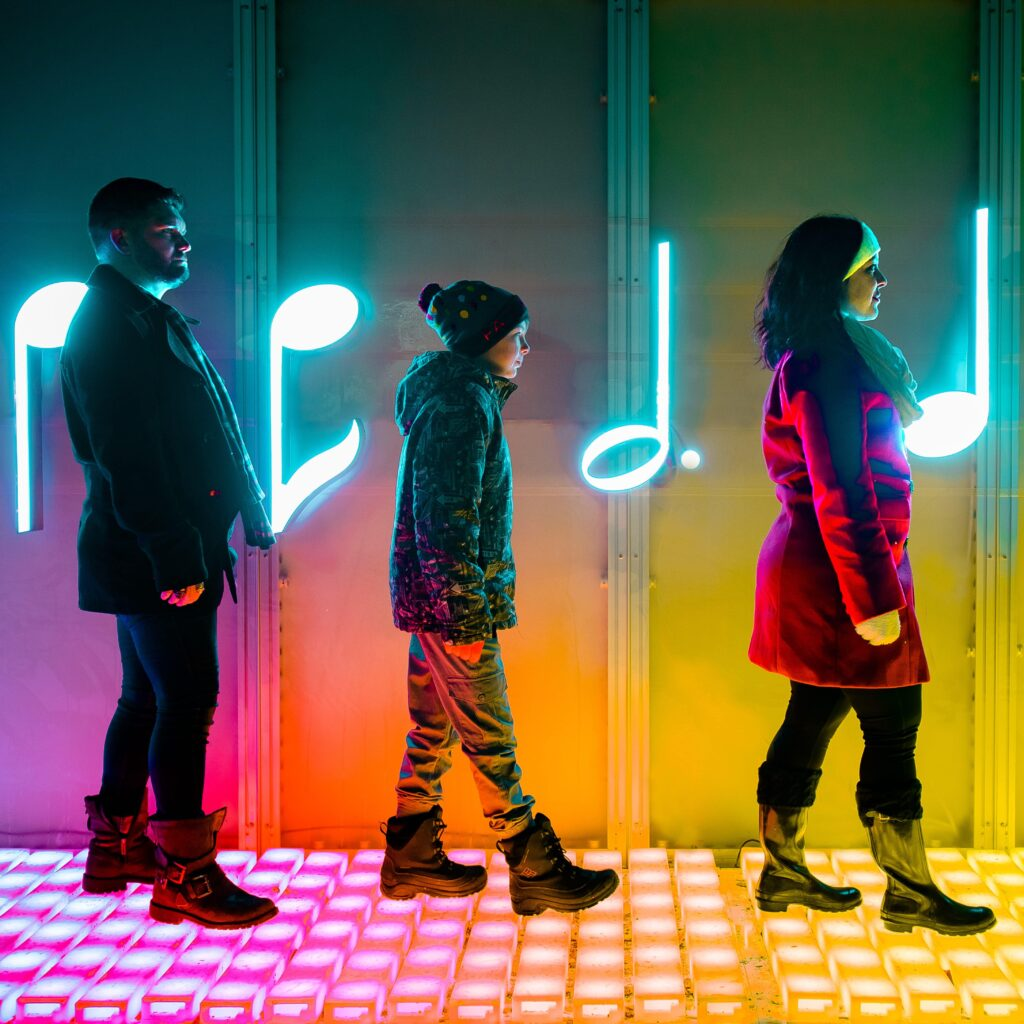 A man, a child, and a woman walk across a colourful LED-illuminated surface, in front of a background of neon music notes