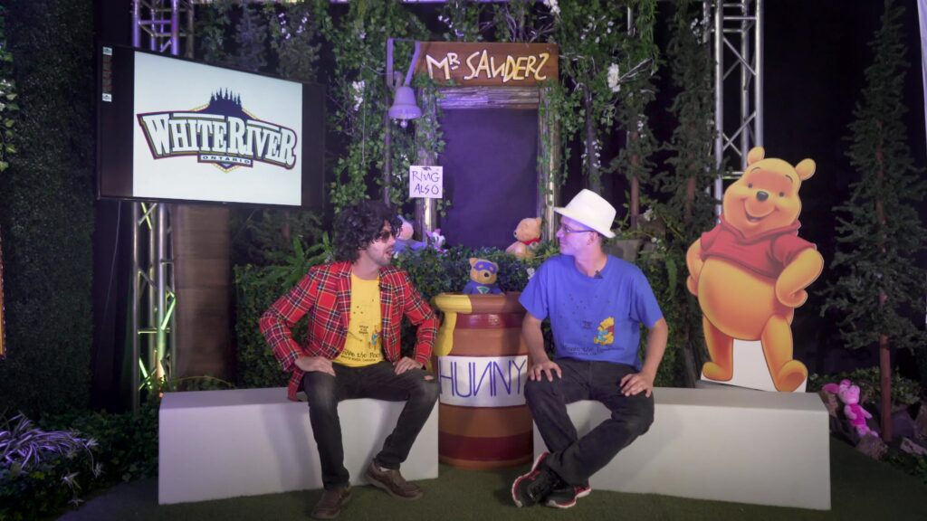 Two men converse in front of a Winnie-the-Pooh themed set during a virtual event