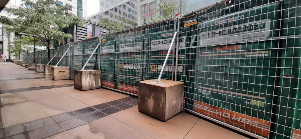 Galvanized temporary fence reinforced with concrete blocks is used as a supporting structure for Echo Barrier acoustic panels.