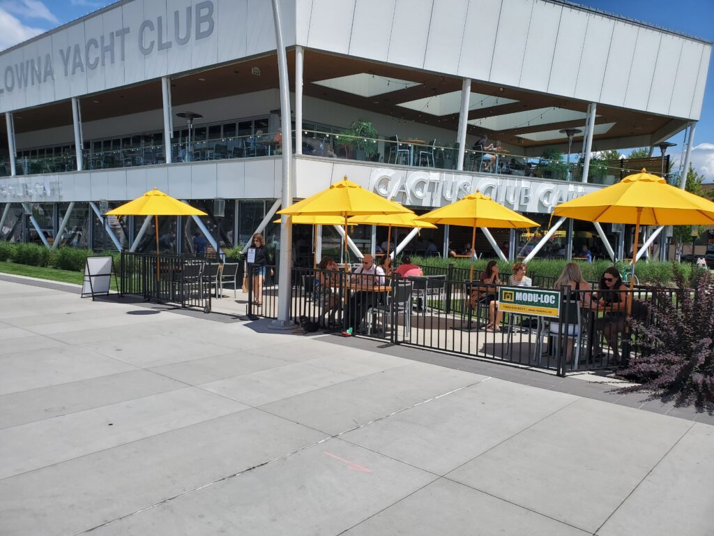 Black temporary fencing encloses a restaurant patio at the Kelowna Yacht Club. Patrons can be seen dining under yellow umbrellas.