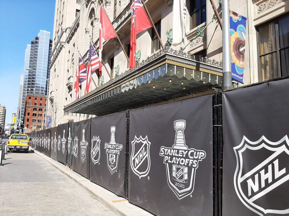 Temporary fence decorated with black branded NHL screeningcreates a barrier in front of a hotel entrance.