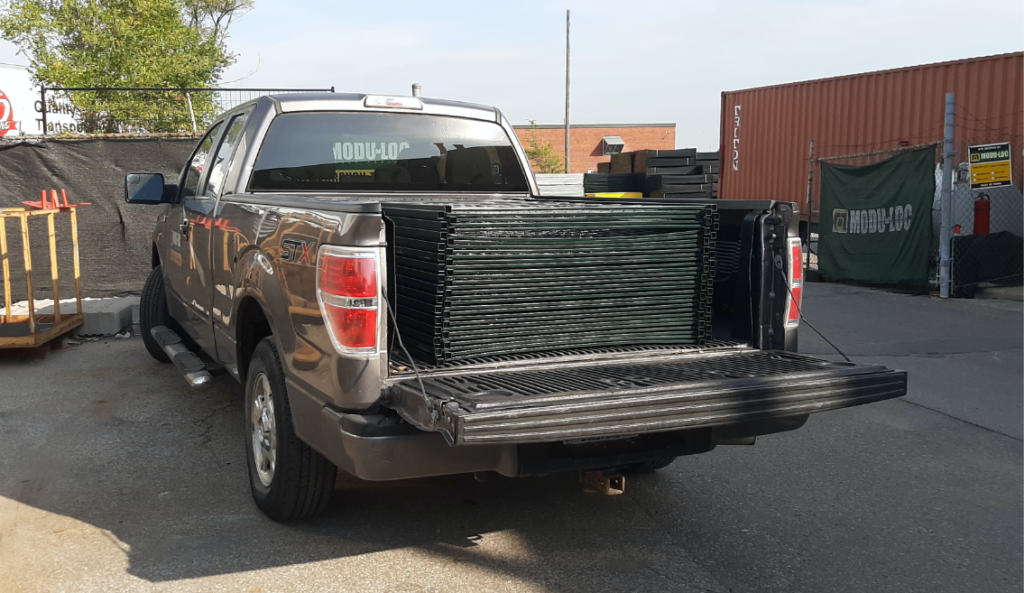 A dark grey pickup truck with a stack of green temporary fence panels in the truck bed.