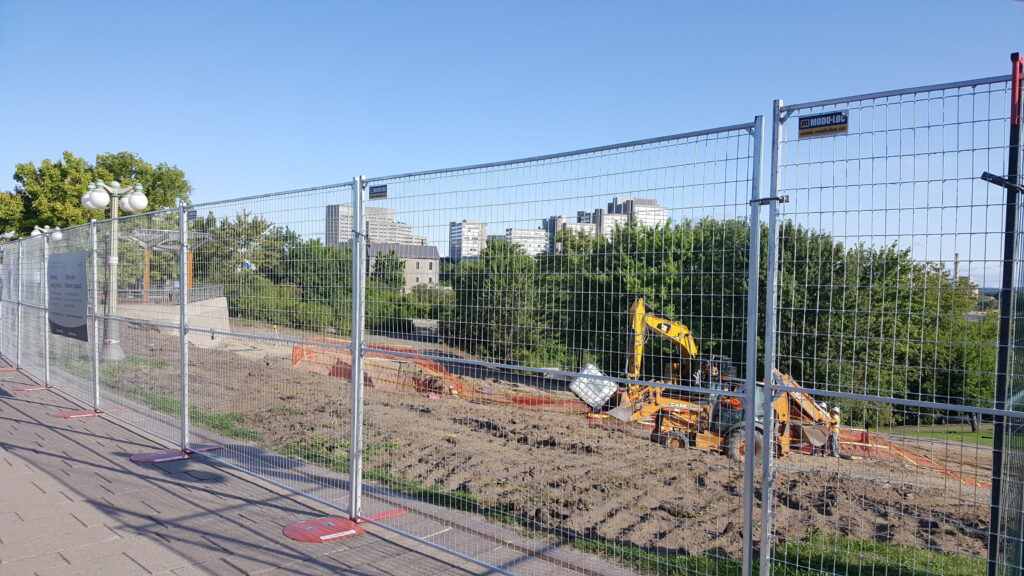 Galvanized temporary fencing surrounds a construction site.